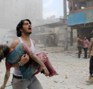 A man carries a young girl who was injured in a reported barrel-bomb attack by regime forces on June 3, 2014 in Kallaseh district of Aleppo (Photo courtesy of New Republic)